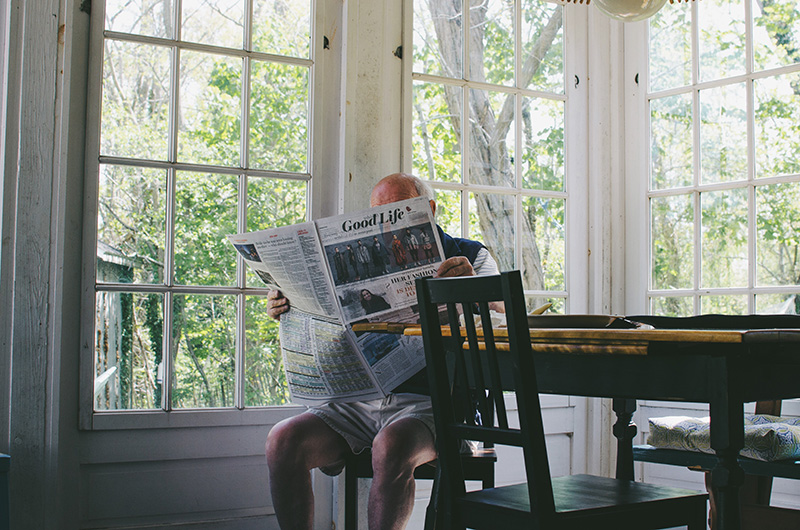 Older man reading newspaper at a table beside large windows
