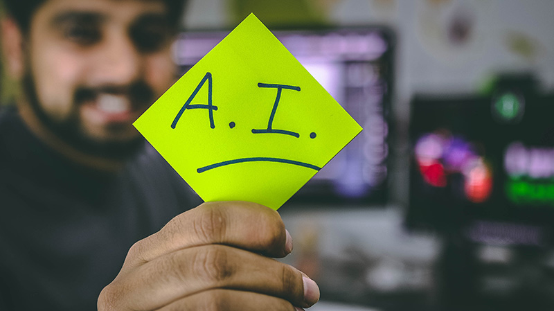 Photo of man holding a post-it note that says A.I.