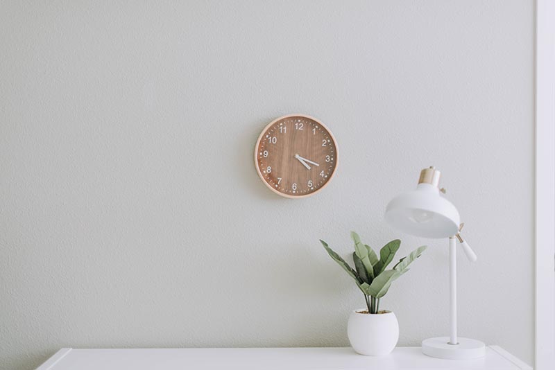 Photo showing clean desk with potted plant, lamp and clock on the wall