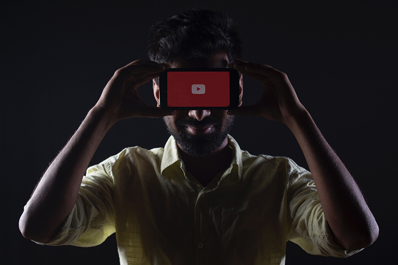 Image of a man holding phone with youtube on