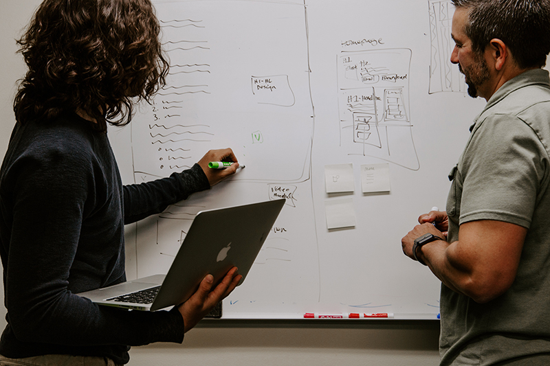 Photo showing people writing on a white board