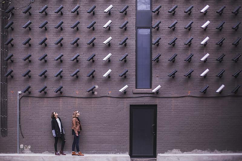 Image of women looking up at wall of security cameras