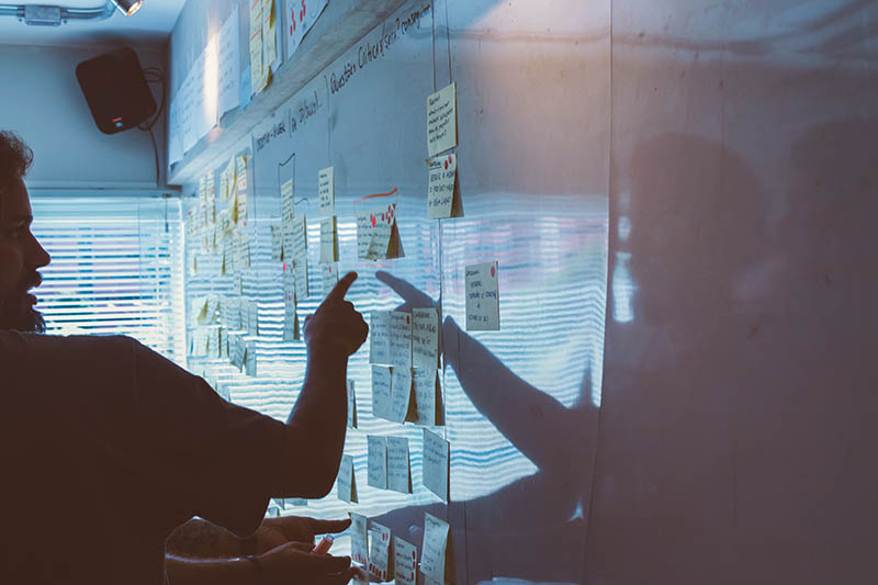 Man pointing at white board with many post-it notes