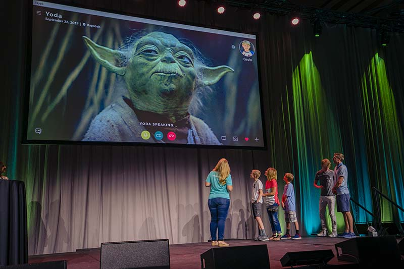 Photo showing Star Wars' Yoda on screen with family looking up from below