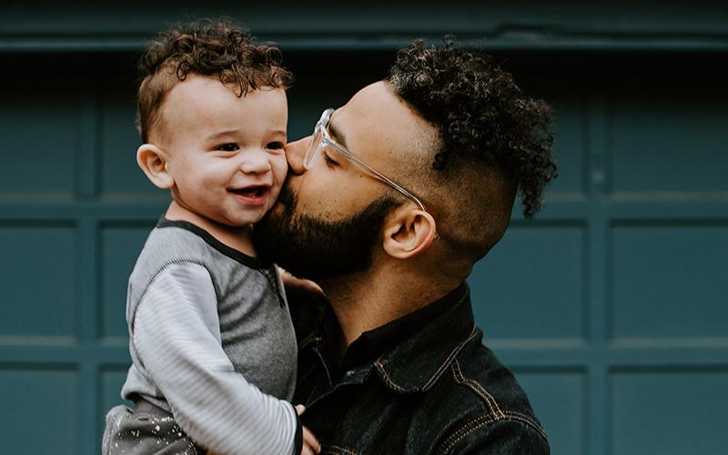 man kissing his son on the cheek