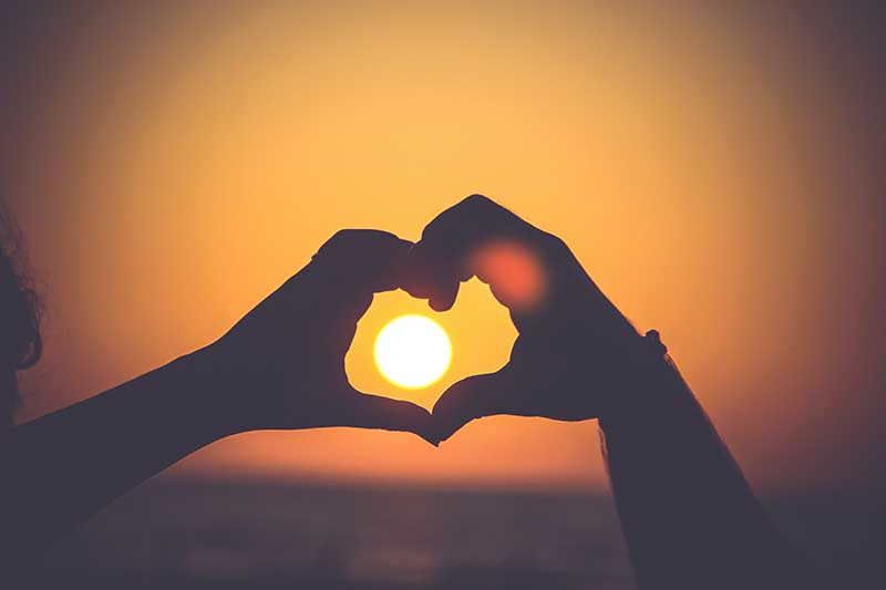 image of hands in heart over sunset