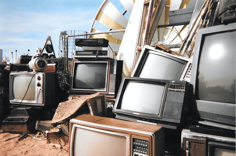 stack of TV in junkyard