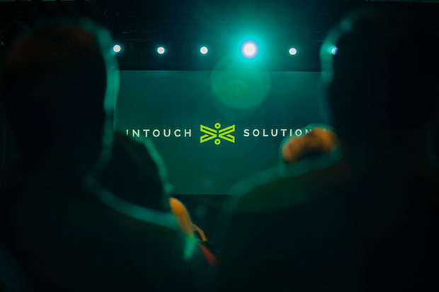 crowd image looking at intouch solutions logo