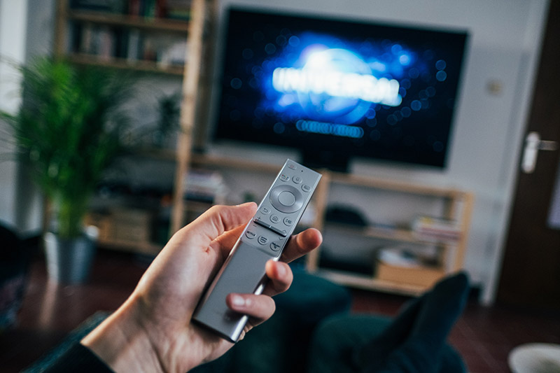 person with remote pointing at tv