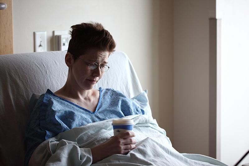 woman in hospital holding pills