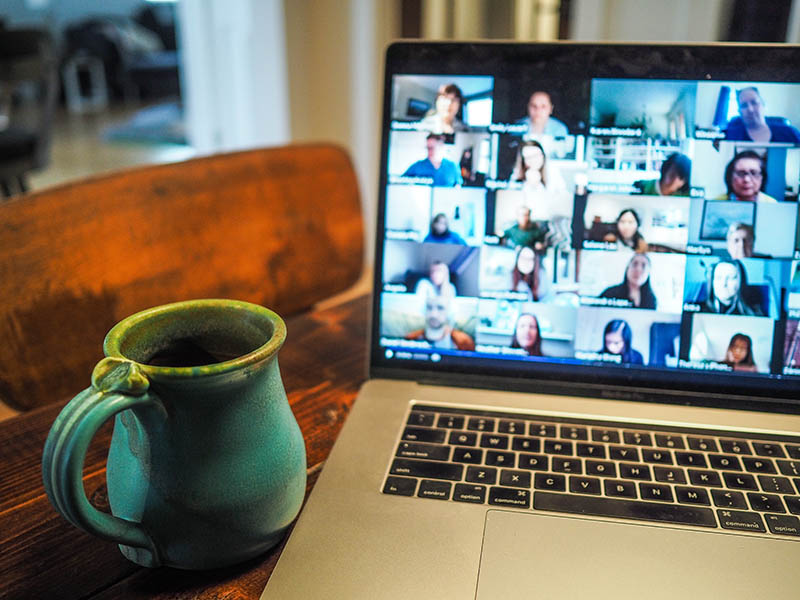 Zoom conference call on laptop next to mug