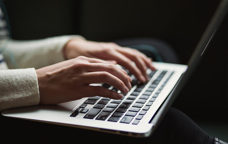 Image of a person typing on keyboard