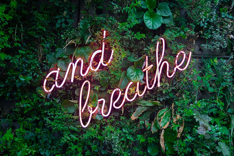 neon sign that says and breathe
