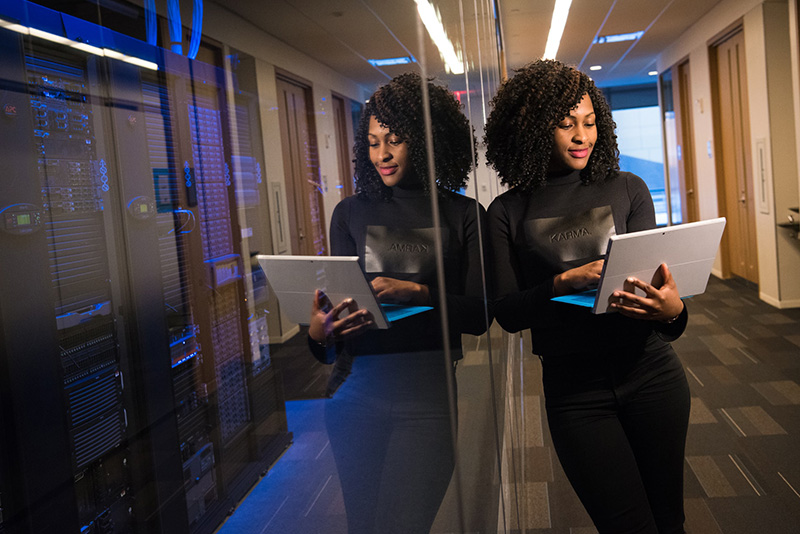 Black woman holds laptop near glassed server room
