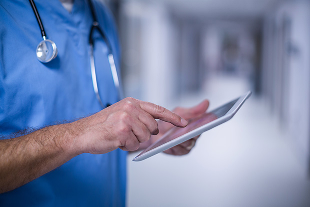 Male doctor interacts with iPad