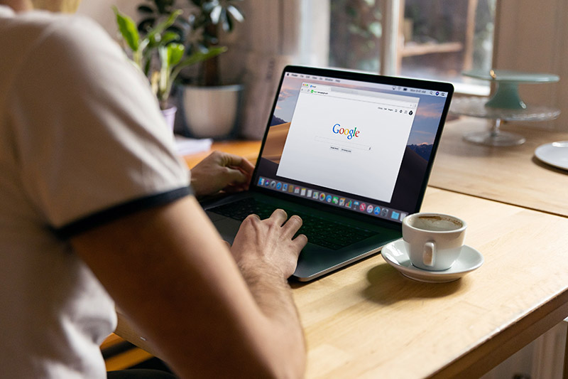 Man searches Google on laptop at desk