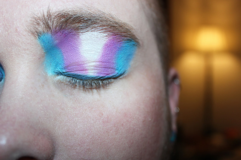 Closeup of eyelid showing the colors of the transgender flag