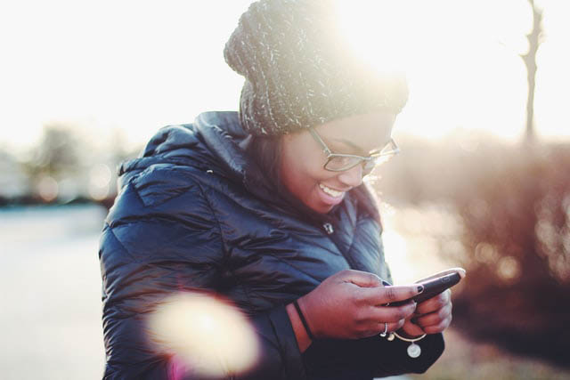 Image showing Black woman smiling at her smartphone
