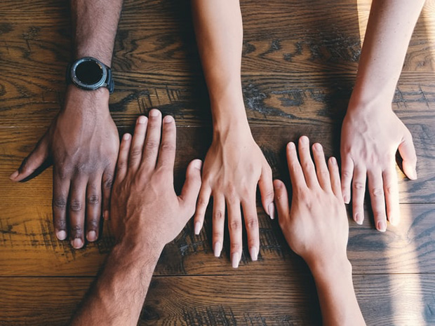 Photo of five hands with different skin tones