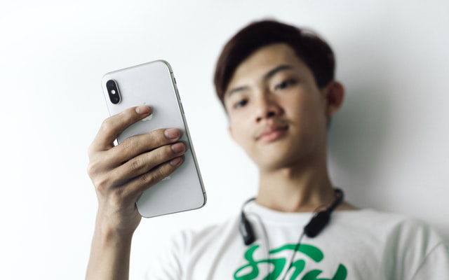 Photo of young Asian man looking at his iPhone