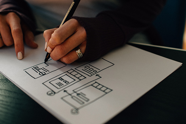 Photo of woman's hand drawing wireframe for website