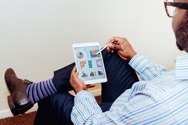 Photo of man looking at charts on iPad