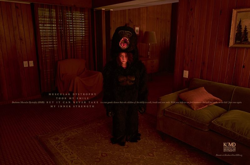 Boy in a bear suit standing in a dark paneled living room