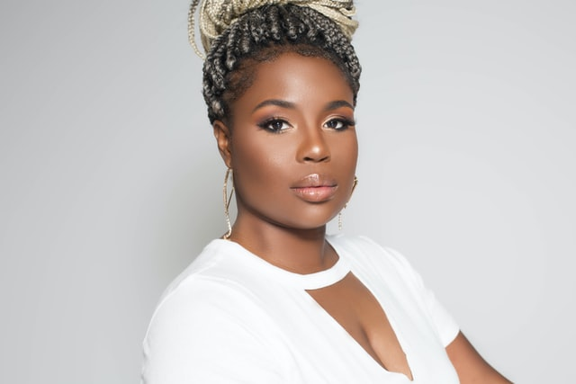Black woman wearing white top, hair pulled up